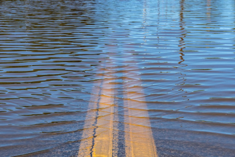 Image of flooded road with yellow road lines visible through the water.